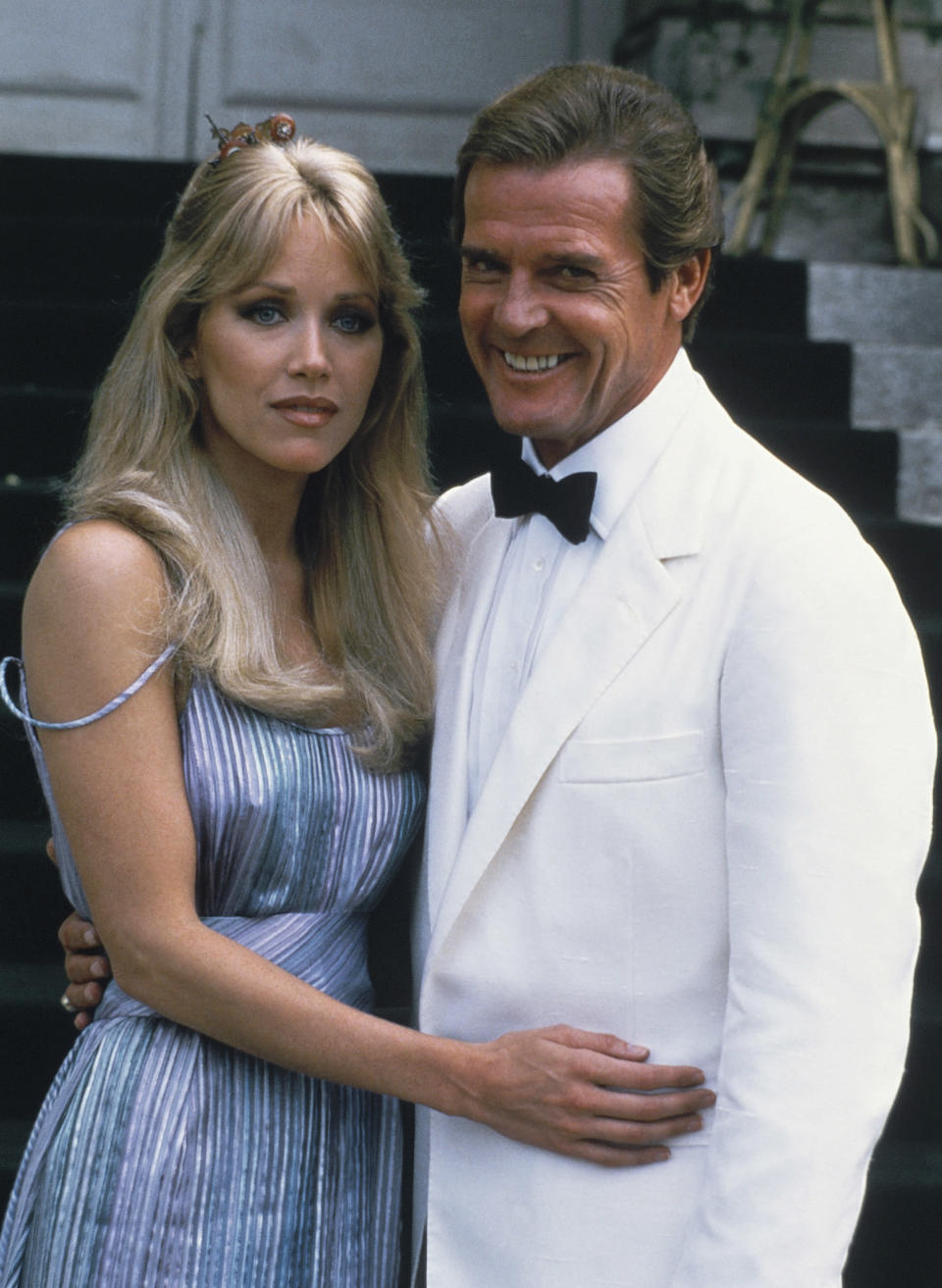"""FILE - Actor Roger Moore, right, poses with his co-star Tanya Roberts from the James Bond film """"A View to a Kill,"""" outside of Château de Chantilly in Chantilly, France on Aug. 17, 1984. Roberts, who captivated James Bond in """"A View to a Kill"""" and had roles on """"Charlie's Angels"""" and """"That '70s Show,"""" died Sunday, Jan. 3, 2021. She was 65. Her death was announced by her publicist. No cause of death was given. (AP Photo/Alexis Duclos, File)"""