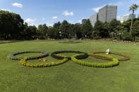 A custodian takes care of plants placed to look like the Olympic rings that local high school students have helped decorate at Hibiya Park in Tokyo Friday, July 16, 2021. (AP Photo/Hiro Komae)