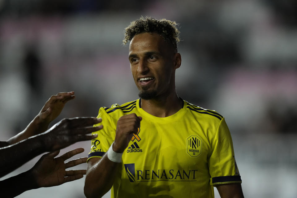 Teammates reach out to congratulate Nashville midfielder Hany Mukhtar after he scored the side's first goal against Inter Miami during the first half of an MLS soccer match, Wednesday, Sept. 22, 2021, in Fort Lauderdale, Fla. (AP Photo/Rebecca Blackwell)