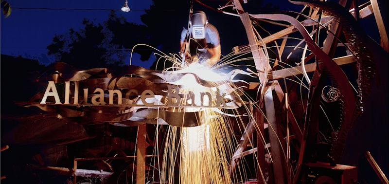 Welder working on metal sculpture with Alliance Bank logo in it.