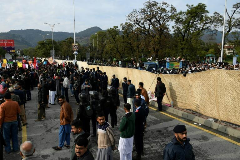 Pakistani riot police in Islamabad separate activists from the Aurat (Women) March (L) and a rival rally organised by Islamists (R, on the other side of a flimsy barrier) -- rocks were hurled against the Aurat group