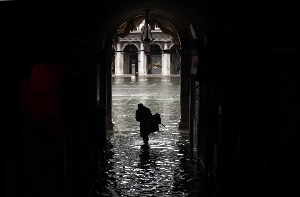 A woman is silhouetted as she walks towards a flooded St. Mark's Square, on the occasion of a high tide, in Venice, Italy, Tuesday, Nov. 12, 2019. (Photo: Luca Bruno/AP)