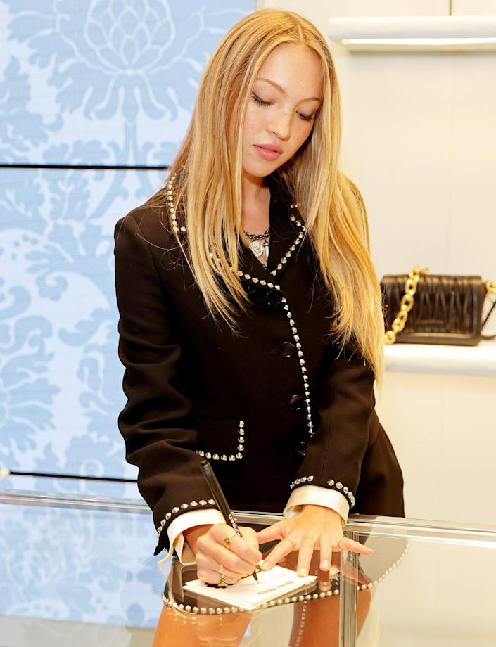 <p>Lila Moss (daughter of Kate) signs by the X on Sept. 16 while hosting a Miu Miu event in London. </p>