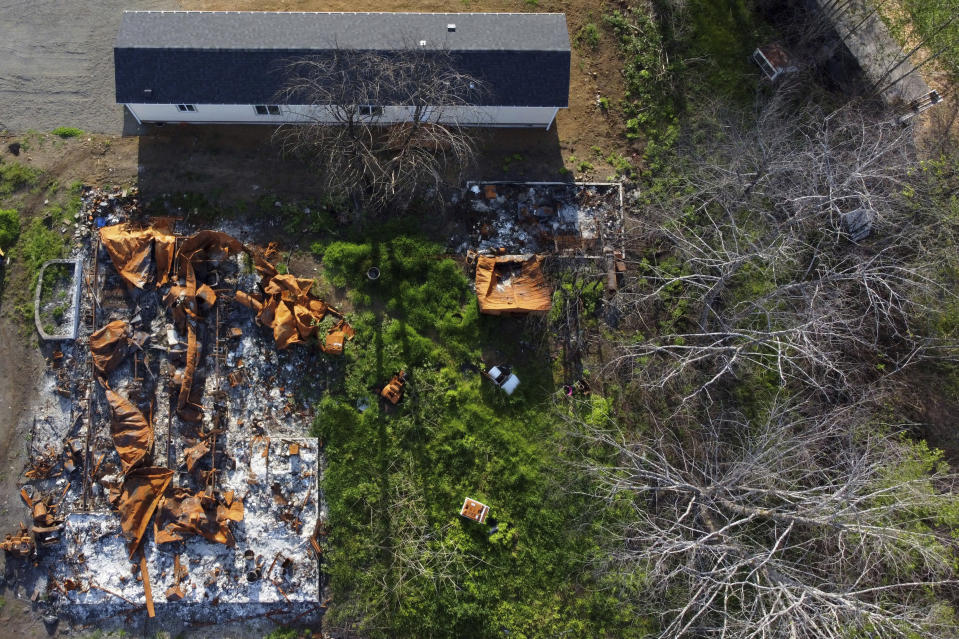 In this aerial photo a new home sits next to a home that burned down during the Echo Mountain fire in Otis, Ore., on Thursday, May. 13, 2020. The small Oregon coast town is still recovering from the devastating fire that destroyed 293 homes. (AP Photo/Craig Mitchelldyer)