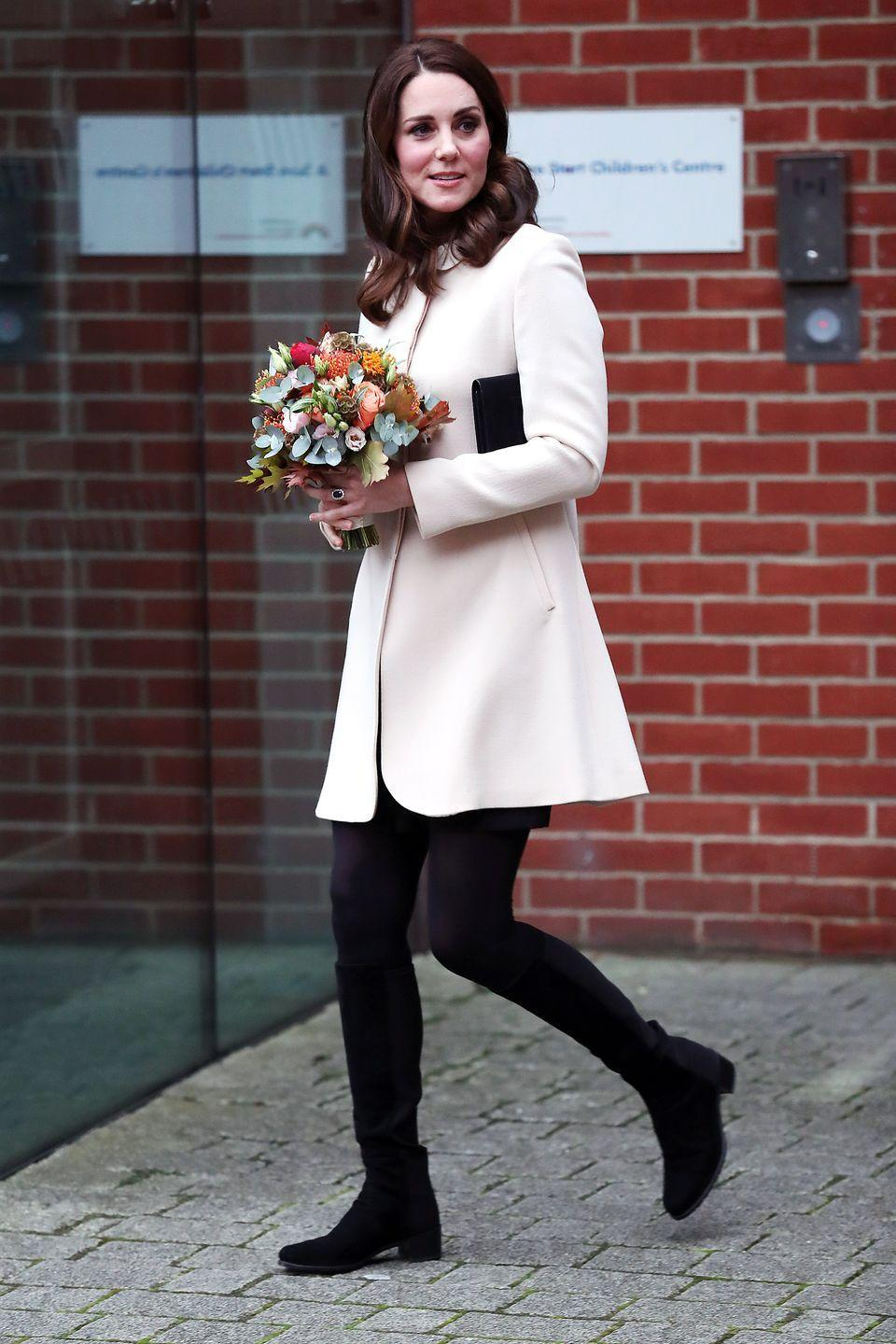 <p>The Duchess wears a pale pink coat, black dress, tights and clutch, and a pair of black suede knee-high boots while leaving the Hornsey Road Children's Centre in London.</p>