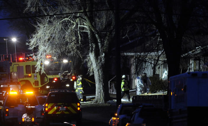 South Bend police and fire officials examine a home where a a plane crash occurred near the South Bend Regional Airport Sunday March 17, 2013 in South Bend, Ind. The private jet apparently experiencing mechanical trouble crashed in a northern Indiana neighborhood, resulting in injuries and striking three homes, authorities and witnesses said. (AP Photo/Joe Raymond)
