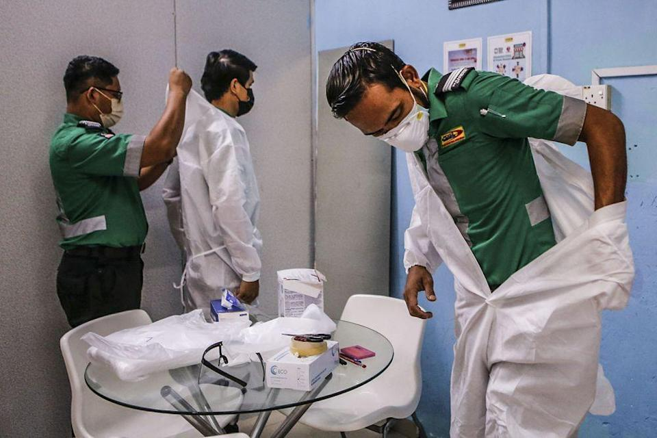 Paramedics don Personal Protection Equipment as they prepare to respond to a Covid-19 related emergency at the company's headquarters in Kuala Lumpur July 5, 2021.