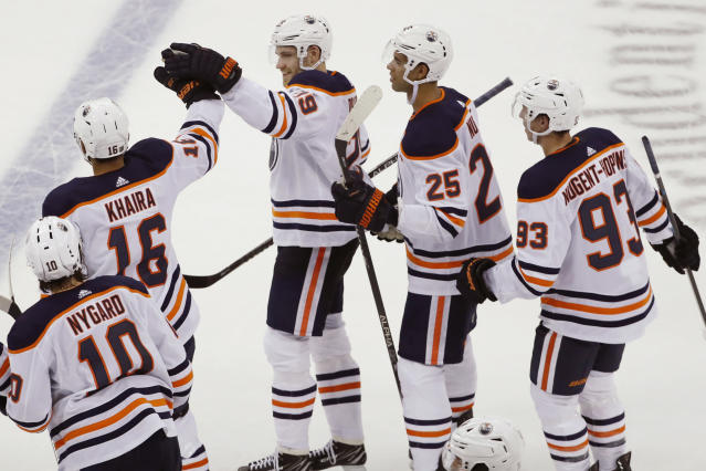 Edmonton Oilers center Leon Draisaitl (29) center, celebrates with left wing Jujhar Khaira (16) and other teammates after scoring against the New Jersey Devils in the shootout of an NHL hockey game Thursday, Oct. 10, 2019, in Newark, N.J. The Oilers won 4-3. (AP Photo/Kathy Willens)