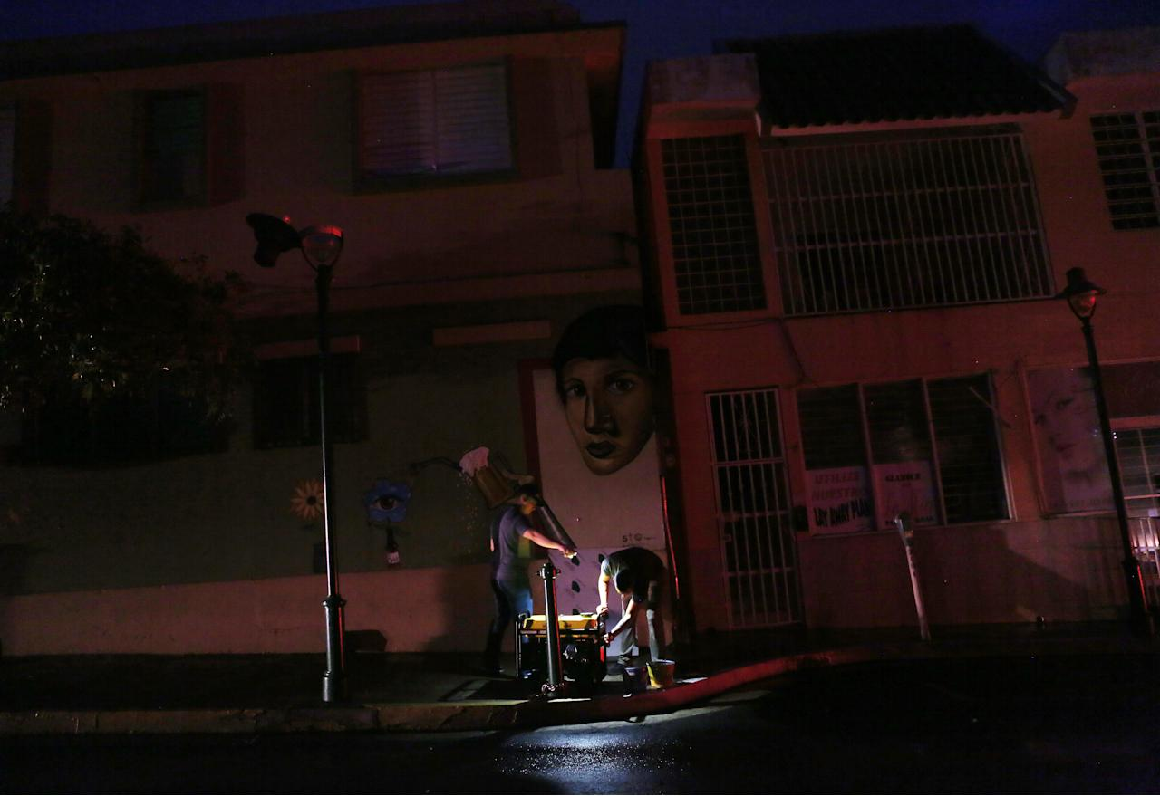 <p>A man prepares to fill a generator with gas to power a bar on a darkened street with car headlights in the distance three weeks after Hurricane Maria hit the island, on Oct. 11, 2017 in Aibonito, Puerto Rico. (Photo: Mario Tama/Getty Images) </p>