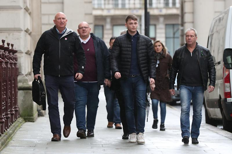 Tim Dunn (second left), the father of teenage motorcyclist Harry Dunn, who was killed when his motorbike crashed into a car outside RAF Croughton in Northamptonshire on August 27, walks with, Harry's stepfather Bruce Charles (right) and family spokesperson Radd Seiger (left) as they arrive at the Foreign and Commonwealth Office in Westminster, London, for a meeting with Foreign Secretary Dominic Raab. (Photo by Jonathan Brady/PA Images via Getty Images)