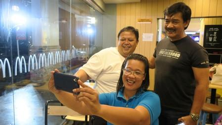 Sonny Parsons, leader of Filipino boyband Hagibis, poses for a photo with fans at a fastfood restaurant in Manila