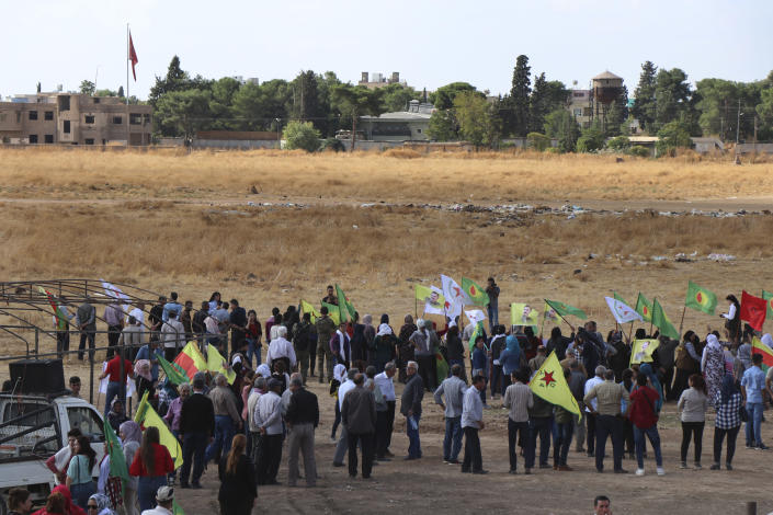 Kurdish citizens wave their group's flags, as they protest against possible Turkish military operation on their areas, at the Syrian-Turkish border, in Ras al-Ayn, Syria, Monday, Oct. 7, 2019. Syria's Kurds accused the U.S. of turning its back on its allies and risking gains made in the fight against the Islamic State group as American troops began pulling back on Monday from positions in northeastern Syria ahead of an expected Turkish assault. (AP Photo)