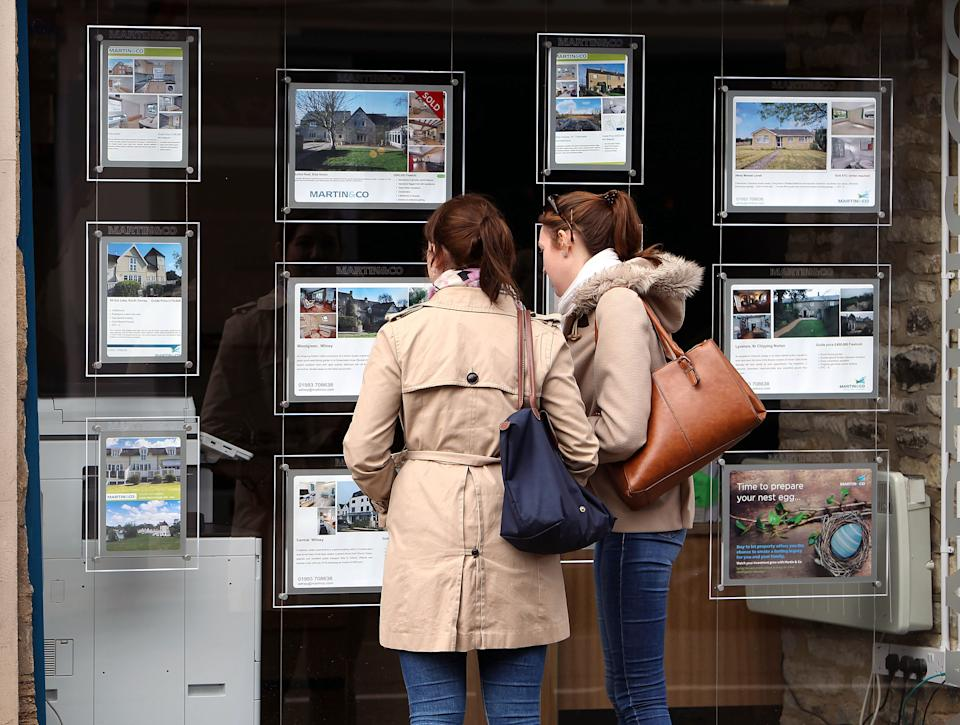 A general picture of two young people looking at an Estate Agents window in Whitney, OXfordshire