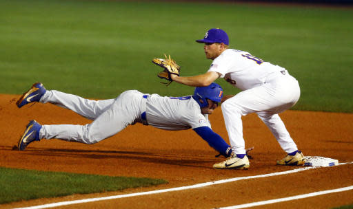 Florida's Deacon Liput dives back to first safely before the tag of LSU first baseman Austin Bain during the first inning of a Southeastern Conference tournament NCAA college baseball game Friday, May 25, 2018, in Hoover, Ala. (AP Photo/Butch Dill)