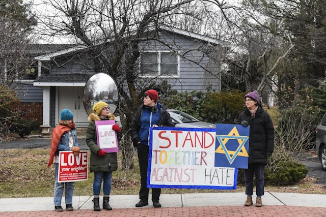 People hold signs of support near the house of Rabbi Chaim Rottenberg on Dec. 29 in Monsey, N.Y., where five people were injured in a knife attack during a Hanukkah party. (Photo: Stephanie Keith/Getty Images)