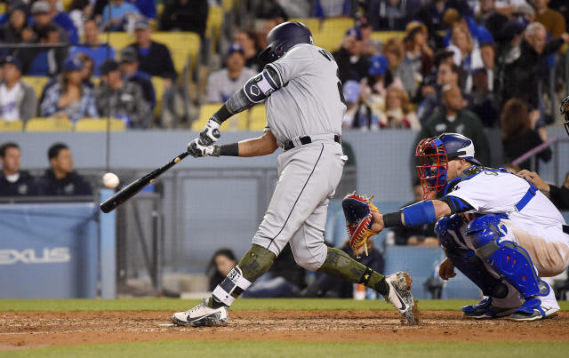 San Diego Padres' Christian Villanueva hits a solo home run in front of Los Angeles Dodgers catcher Yasmani Grandal during the eighth inning of a baseball game Saturday, May 26, 2018, in Los Angeles. (AP Photo/Mark J. Terrill)