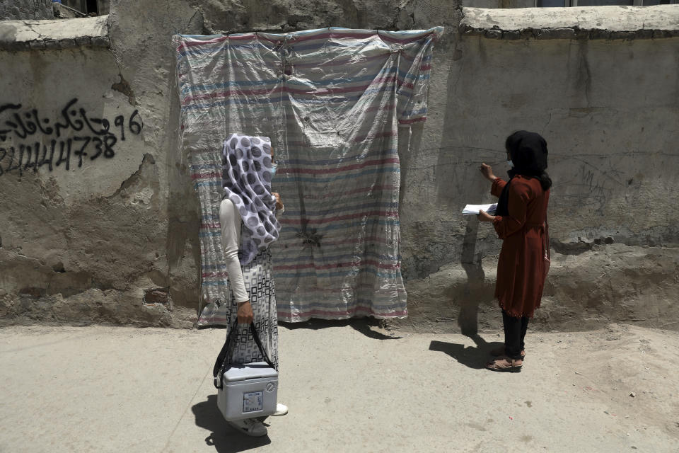Health workers go door to door during a polio vaccination campaign in the old part of Kabul, Afghanistan, Tuesday, June 15, 2021. Gunmen on Tuesday targeted members of polio teams in eastern Afghanistan, killing a number of staffers, officials said. (AP Photo/Rahmat Gul)