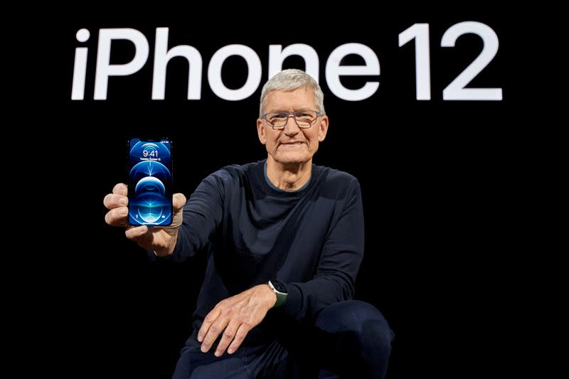 FILE PHOTO: Apple CEO Tim Cook poses with the iPhone 12 Pro at Apple Park in Cupertino