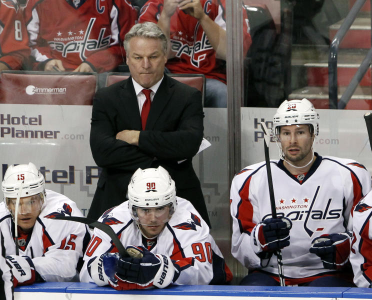 FILE - In this Dec. 5, 2011 file photo, Washington Capitals head hockey coach Dale Hunter, rear, looks on during the first period of an NHL hockey game against the Florida Panthers, in Sunrise, Fla. Hunter is finished as coach of the Washington Capitals after less than one full season, telling the team he wants to return to his family in Canada. (AP Photo/Wilfredo Lee, File)