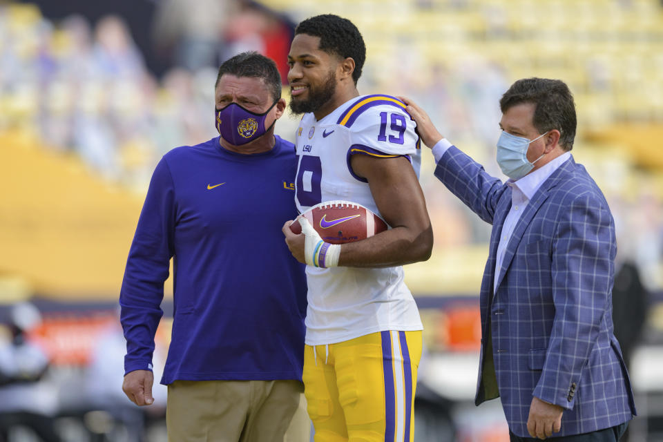 LSU head coach Ed Orgeron takes a senior portrait with LSU linebacker Jabril Cox (19) and LSU Athletic Director Scott Woodward before an NCAA college football game against Mississippi in Baton Rouge, La., Saturday, Dec. 19, 2020. (AP Photo/Matthew Hinton)
