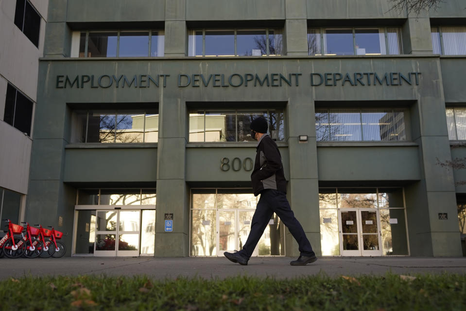 FILE - In this Dec. 18, 2020, file photo, a person passes the office of the California Employment Development Department in Sacramento, Calif. On Tuesday, Jan. 26, 2021, California State Auditor Elaine Howle released a report saying that the EDD might have overpaid millions of people since March 2020 after it stopped enforcing eligibility rules so they could process claims faster. (AP Photo/Rich Pedroncelli, File)