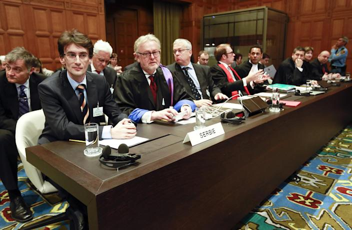 Members of the Serbian delegation, from left: Sasa Orbadovic, William Schabas, Andreas Zimmermann, Christian Tams and Wayne Jordash await the start of public hearings at the International Court of Justice (ICJ) in The Hague, Netherlands, Monday, March 3, 2014. Croatia is accusing Serbia of genocide during fighting in the early 1990's as the former Yugoslavia shattered in spasms of ethnic violence, in a case at the United Nations' highest court that highlights lingering animosity in the region. Croatia is asking the ICJ to declare that Serbia breached the 1948 Genocide Convention when forces from the former Federal Republic of Yugoslavia attempted to drive Croats out of large swaths of the country after Zagreb declared independence in 1991. (AP Photo/Jiri Buller)