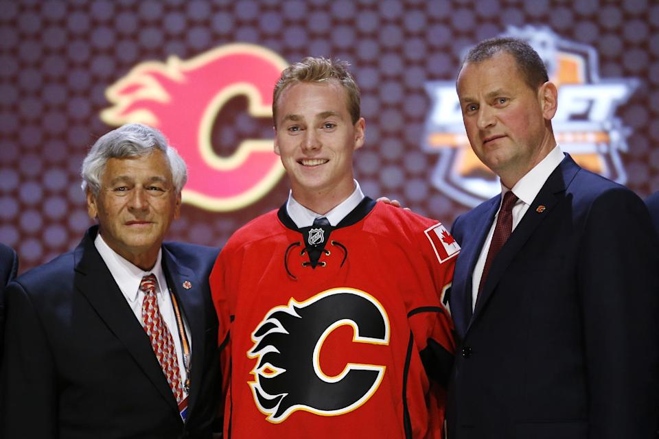 Samuel Bennett stands with Calgary Flames officials after being chosen fourth overall during the first round of the NHL hockey draft, Friday, June 27, 2014, in Philadelphia. (AP Photo/Matt Slocum)