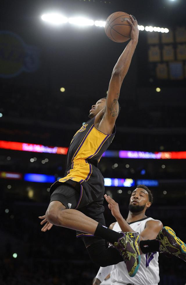 Los Angeles Lakers guard Kent Bazemore, left, goes up for a dunk as Sacramento Kings forward Derrick Williams defends during the first half of an NBA basketball game, Friday, Feb. 28, 2014, in Los Angeles. (AP Photo/Mark J. Terrill)