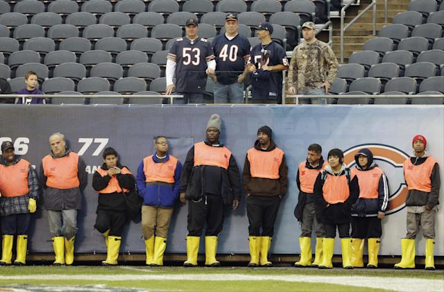 Soldier Field groundskeepers line up against the wall and a few Chicago Bears fans watch as players warm up before an NFL football against the Baltimore Ravens, Sunday, Nov. 17, 2013, in Chicago. (AP Photo/Nam Y. Huh)