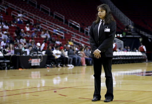 In this photo taken on March 15, 2014, Toyota Center security guard Sandra Rivera stands on the court while keeping an eye on fans during a timeout in the first half of an NCAA college basketball game between Texas Southern and Prairie View A&M in the championship of the Southwestern Athletic Conference tournament in Houston. Security firms charged with protecting college and professional sports venues are monitoring social media more than ever to prepare for everything from a garden-variety court storming to something much more dangerous. (AP Photo/David J. Phillip)