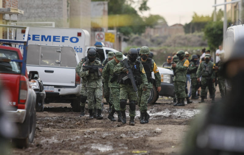 Members of the national guard walk near an unregistered drug rehabilitation center after a shooting in Irapuato, Mexico, Wednesday, July 1, 2020. Gunmen burst into the rehab center and opened fire, killing more than 20 and wounding several more. (AP Photo/Mario Armas)