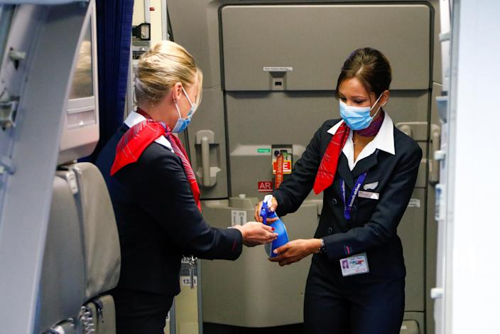 Flight attendants wearing face masks sanitise their hands inside a plane at the Zaventem International Airport, as Belgium eases restrictions aimed to contain the spread of the coronavirus disease (COVID-19) outbreak, near Brussels, Belgium June 15, 2020. REUTERS/Francois Lenoir