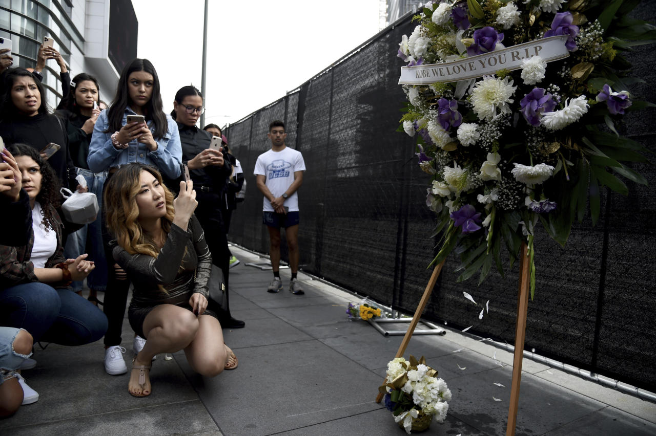 A group of fans gather near a makeshift memorial for NBA legend Kobe Bryant outside the Staples Center in Los Angeles, just before the Grammy Awards were set to take place on Jan. 26, 2020. (AP Foto/Chris Pizzello)