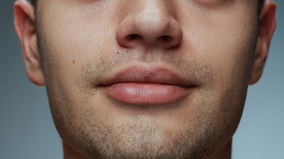 Close-up portrait of young man isolated on grey studio background. Caucasian male model's face and lips. Concept of men's health and beauty, self-care, body and skin care.