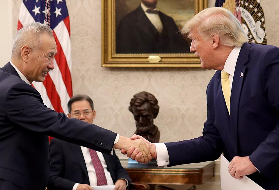 """WASHINGTON, DC - OCTOBER 11:  U.S. President Donald Trump shakes hands with Chinese Vice Premier Liu He after announcing a """"phase one"""" trade agreement with China in the Oval Office at the White House October 11, 2019 in Washington, DC.  China and the United States have slapped each other with hundreds of billions of dollars in tariffs since the current trade war began between the world's two largest national economies in 2018. (Photo by Win McNamee/Getty Images)"""