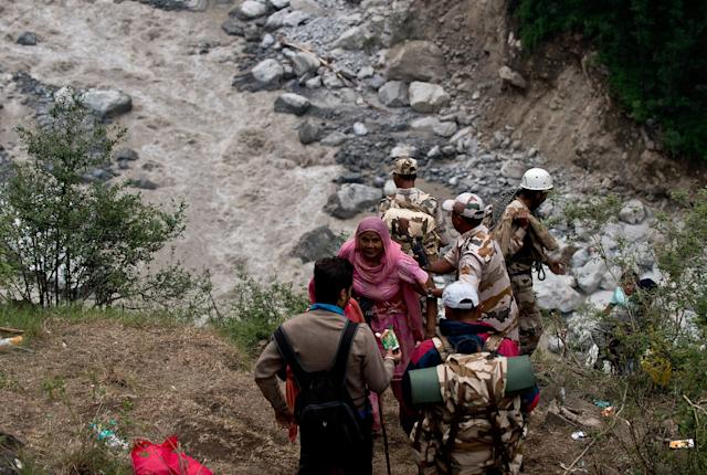 Indo-Tibetan Border Police personnel provide assistance as stranded Indian pilgrims make their way up a mountain after a section of road was washed away in Govind Ghat on June 23, 2013. Bad weather hampered rescue operations June 23 in northern India where up to 1,000 people are feared to have died in landslides and flash floods that have left pilgrims and tourists stranded without food or water. AFP PHOTO/MANAN VATSYAYANA