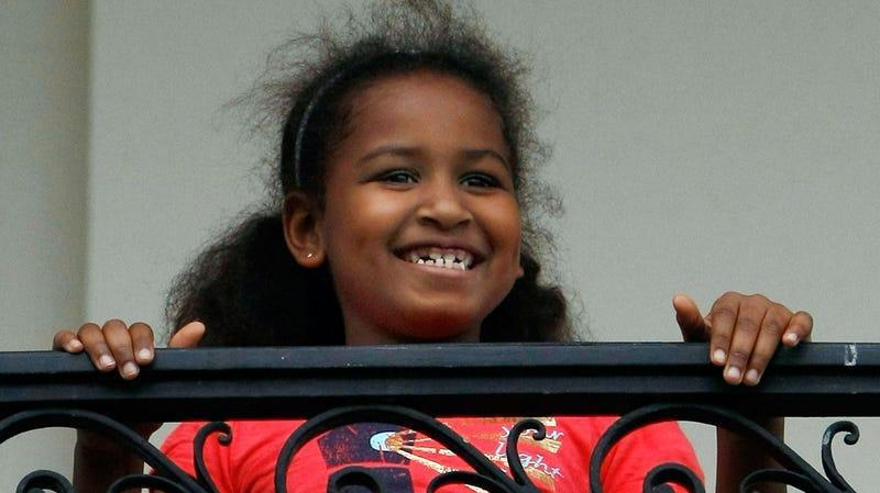 U.S. President Barack Obama's daughter Sasha watches him from the Truman Balcony after he arrived on the south lawn of the White House via Marine One May 14, 2009 in Washington, DC.
