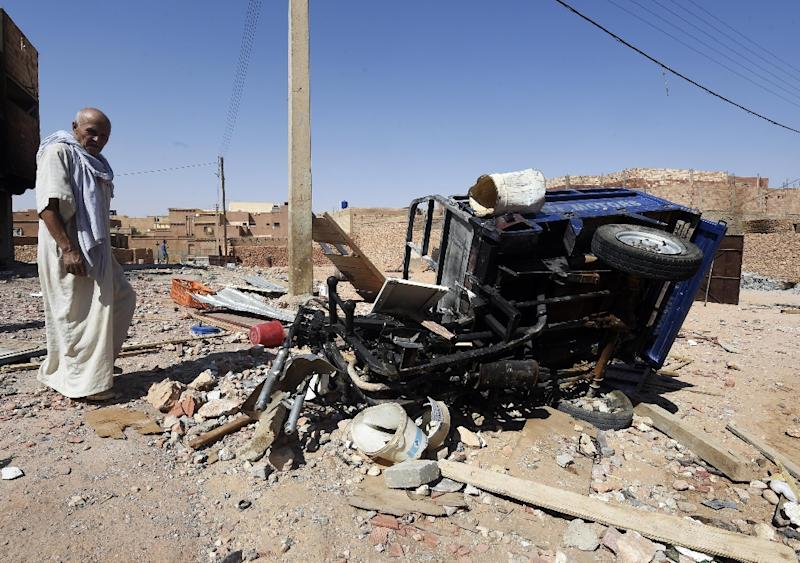 A man from the Arab community walks past the wreckage of a vehicle on July 9, 2015, following clashes between Berbers and Arabs in the Algerian town of Guerara (AFP Photo/Farouk Batiche)