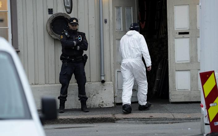 A police technician enters a building in the town center following the deadly attack in Kongsberg - REUTERS