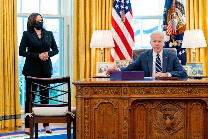 President Joe Biden, accompanied by Vice President Kamala Harris, looks up after signing the American Rescue Plan.