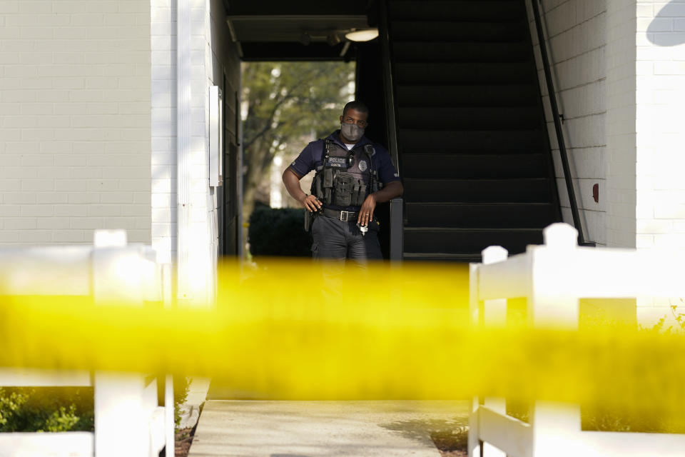 A police officer stands behind police tape outside the apartment of Navy Petty Ofc. 3rd Class Fantahun Girma Woldesenbet, assigned to Fort Detrick in Frederick, Md., Tuesday, April 6, 2021. Authorities say the Navy medic shot and wounded two U.S. sailors at a military facility before fleeing to a nearby Army base where security forces shot and killed him. (AP Photo/Carolyn Kaster)