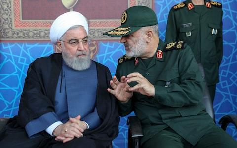 President Hassan Rouhani, left, listens to chief of the Revolutionary Guard Gen. Hossein Salami at a military parade marking 39th anniversary of outset of Iran-Iraq war - Credit: Office of Iranian Presidency