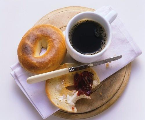 plain bagel with jam and butter and mug of black coffee
