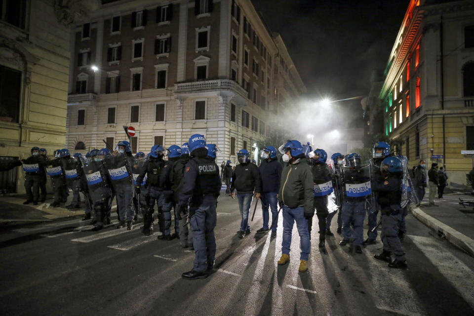 Police officers patrol during a protest called by Forza Nuova far right group against the government restriction measures to curb the spread of COVID-19, in Rome Saturday, Oct. 24, 2020. A midnight-to-5 a.m. curfew in Italy's Lazio region, which includes Rome, begins on Friday and lasts for 30 days, under orders from regional governor Nicola Zingaretti. (Cecilia Fabiano/LaPresse via AP)
