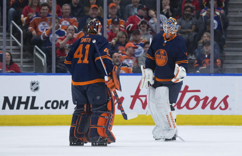 Edmonton Oilers goalie Mikko Koskinen, right, of Finland, skates off the ice after being replaced by Mike Smith after allowing a fourth goal to the Calgary Flames, during the second period of an NHL hockey game Friday, Dec. 27, 2019, in Edmonton, Alberta. (Darryl Dyck/The Canadian Press via AP)