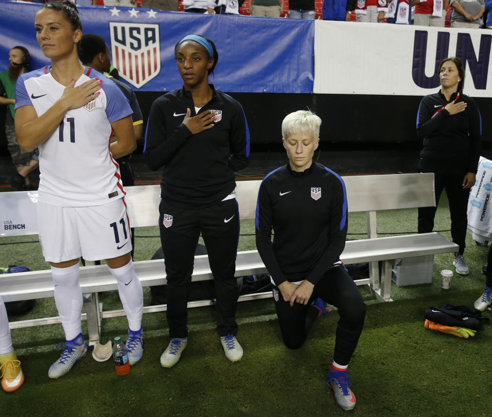 "FILE - In this Sunday, Sept. 18, 2016, file photo, USA's Megan Rapinoe, right, kneels next to teammates Ali Krieger (11) and Crystal Dunn (16) as the U.S. national anthem is played before an exhibition soccer match against Netherlands, in Atlanta. The U.S. Soccer Federation has adopted a policy that says national team players ""shall stand respectfully"" during national anthems. The policy was approved in February 2017 but came to light on Saturday, March 4, 2017, before the U.S. women's national team played England in a SheBelieves Cup match. The policy comes after midfielder Rapinoe knelt during the anthem at a pair of national team matches in 2016. (AP Photo/John Bazemore, File)"