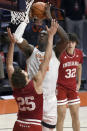 Illinois center Kofi Cockburn (21) shoots as Indiana's forward Race Thompson (25) and guard Trey Galloway (32) defend during the second half of an NCAA college basketball game Saturday, Dec. 26, 2020, in Champaign, Ill. (AP Photo/Holly Hart)