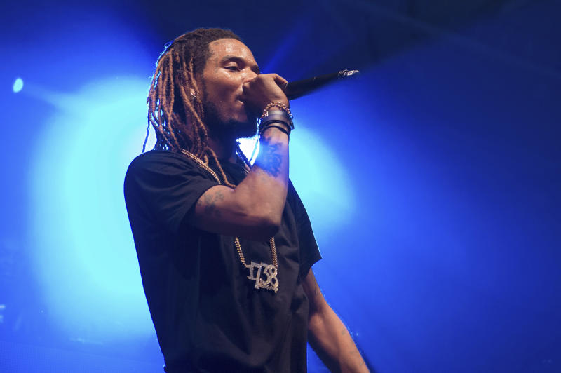 "FILE - In this Saturday, Dec. 26, 2015, file photo, Rapper Fetty Wap performs in concert at Pier 36 in New York. Hip-hop promoter Raheem Thomas was arrested after a shooting Sunday, March 26, 2017, involving Fetty Wap in Paterson, N.J. Thomas is also facing an armed robbery charge, according to Passaic County prosecutors. A photo posted to Thomas' Instagram account showed a masked man wearing what appears to be Fetty Wap's signature ""1738"" pendant. (Photo by Scott Roth/Invision/AP, File)"