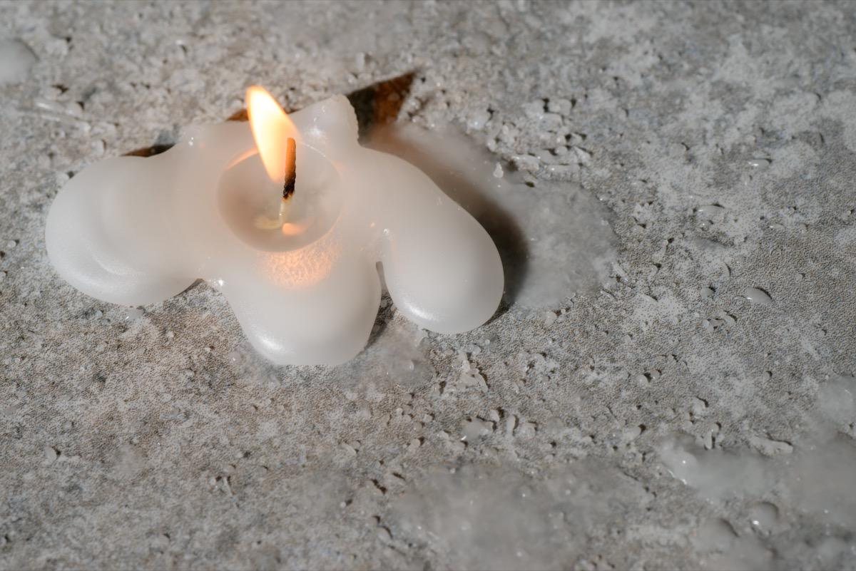 "If you ever spill candle wax on a <a href=""https://bestlifeonline.com/storage-furniture/?utm_source=yahoo-news&utm_medium=feed&utm_campaign=yahoo-feed"">piece of furniture</a>, don't risk ruining its finish by trying to scrape it off. Instead, fill a plastic bag with ice cubes, place it over the wax, and let it sit for a few minutes. Once the wax has sufficiently cooled and hardened, you can pick it up easily without ruining your furniture for good."
