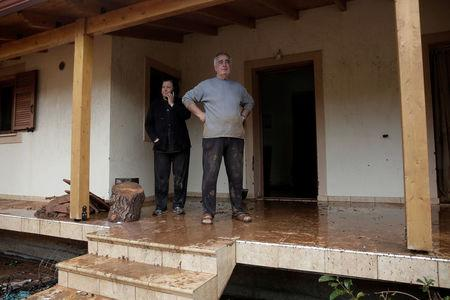 Locals stand at the entrance of their destroyed house following a heavy rainfall in the town of Mandra, Greece, November 15, 2017. REUTERS/Alkis Konstantinidis